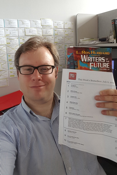 Auston holding up the Publishers Weekly Bestseller list for Writers of the Future Vol 31