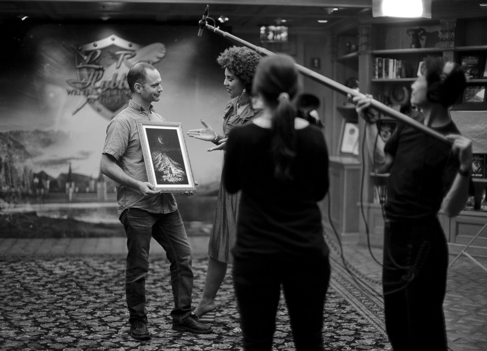 "Holding the illustration for his story, ""Moonlight One,"" while being interviewed by Joy Villa. Photo by Thorsten Overgaard."