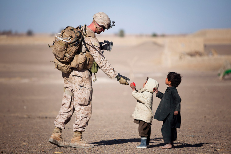 Small kids handing soldier a ball