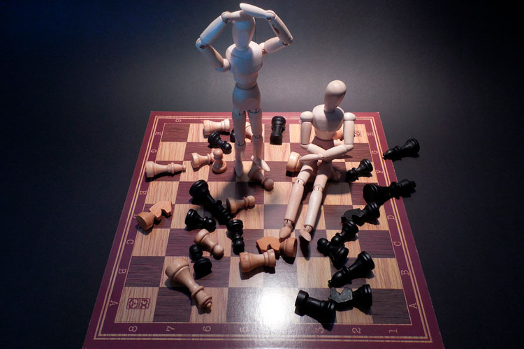 two wooden men figures amongst chess pieces