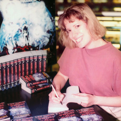 Beverly Suarez-Beard autographing copies of Writers of the Future Volume 11.