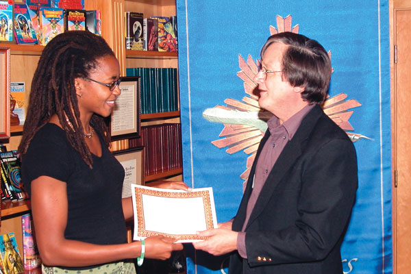 Judge Tim Powers presents Nnedi Okorafor with her workshop certificate.