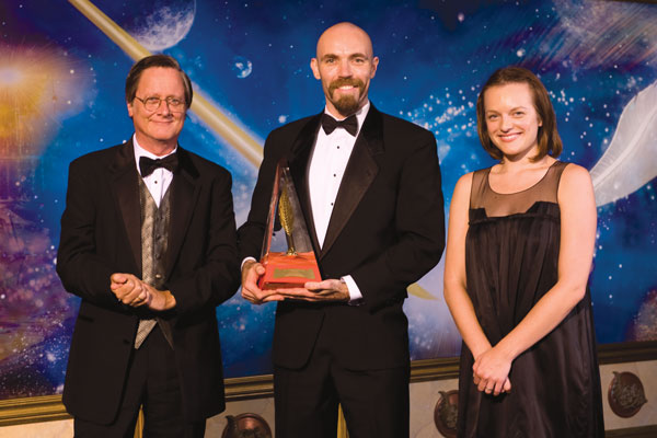 Tim Powers and actress Elisabeth Moss present the Gold Award to Ian McHugh.