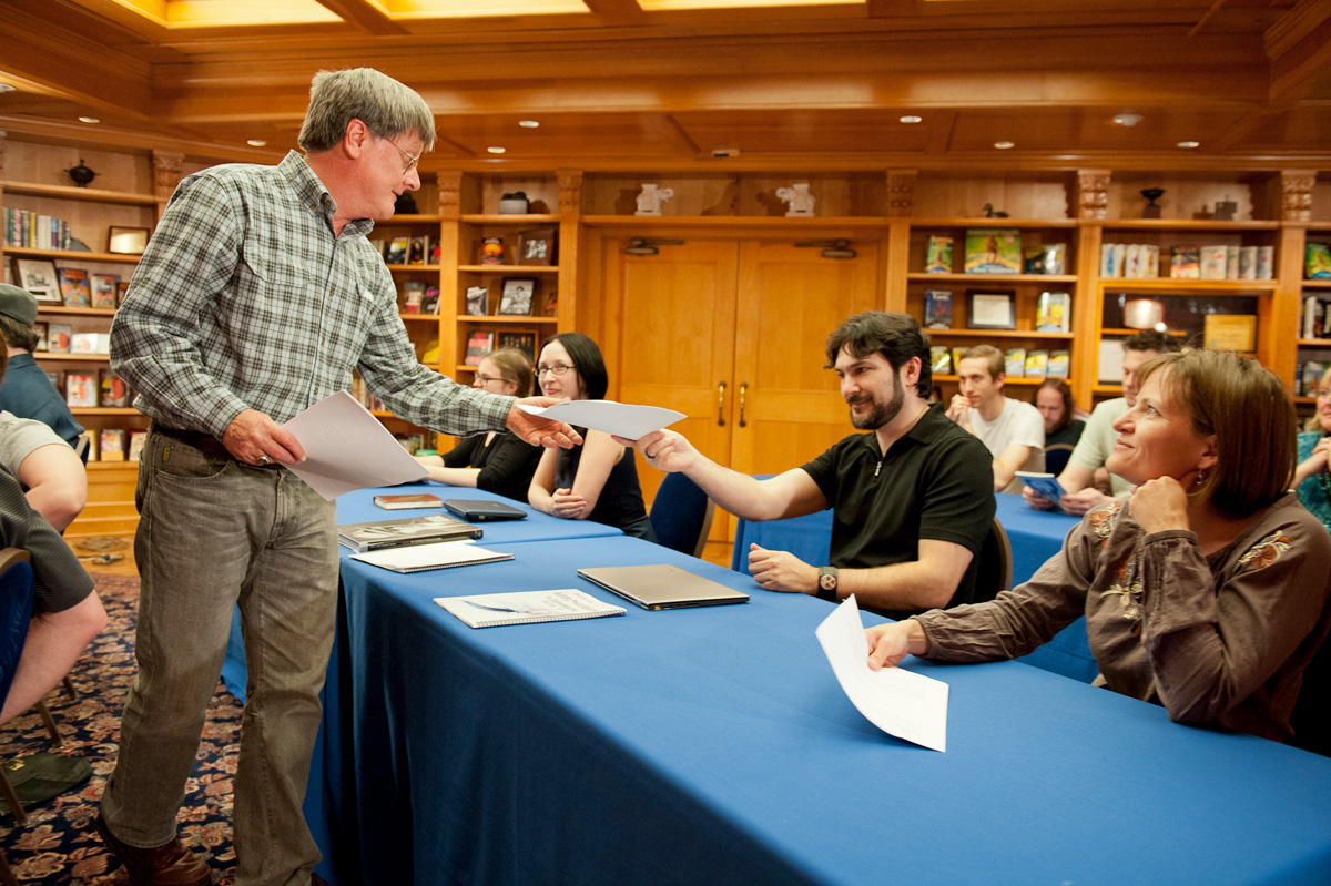 Tim Powers picks up the printouts of the stories from the writer winners.