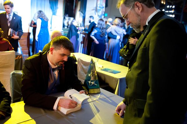 Daniel signing a copy of Writers of the Future Volume 31 at the Annual Awards after-event party.