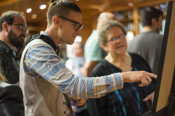 Illustrator Killian McKeown looking at his illustration with contest judge Nina Kiriki Hoffman.