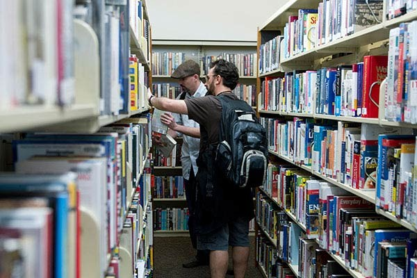 Daniel Davis (left) and Tim Napper (right) comb through the shelves in search of the applicable books.